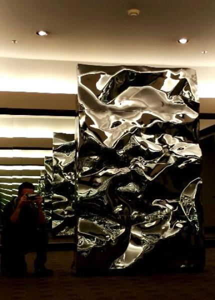 A large metal sculpture between two mirrors